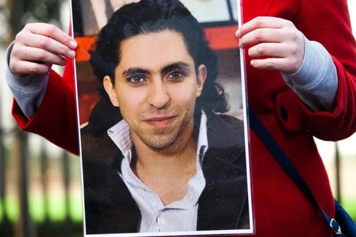 Um homem segurando uma fotografia impressa de Raif Badawi