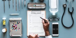 An areal view of various medical equipment including a patient chart, medication, a stethoscope, a pair of eyeglasses, and an iphone.