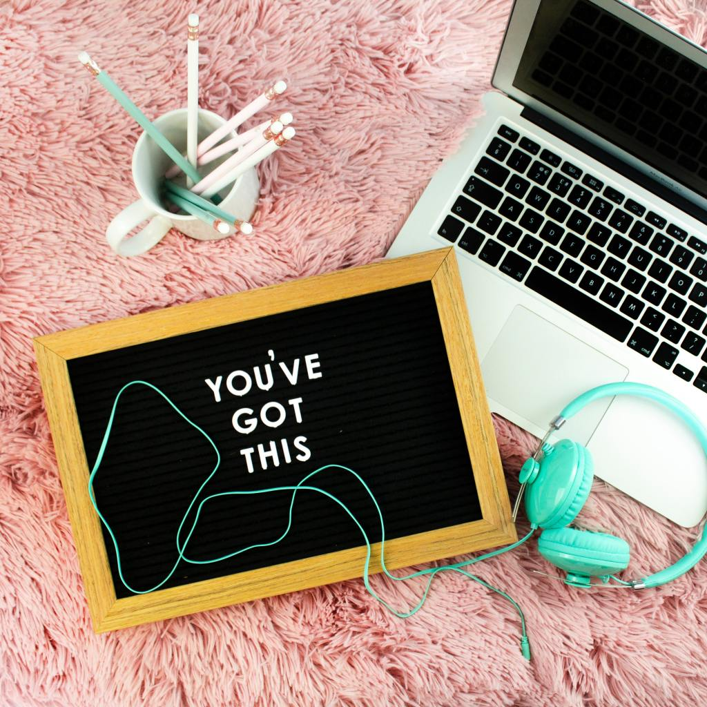 "a laptop with a sign reading ""you've got this"" and a pair of headphones"