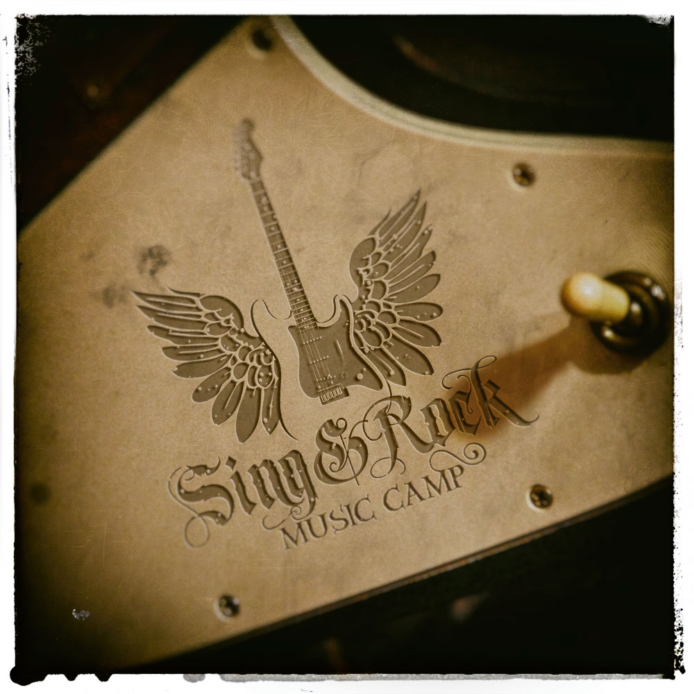 sing and rock music camp logo carved in guitar