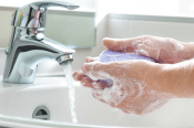 Person with soapy hands rinsing under a sink