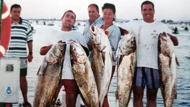 Néstor Santos exhibe cinco grandes corvinas junto con otros pescadores en sus años de juventud