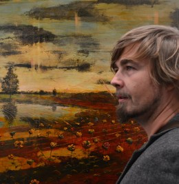 Photograph of artist Jernej Forbici in front of one of his paintings.