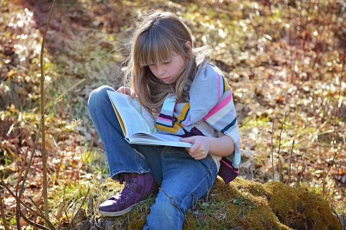 Child reading a book outdoors