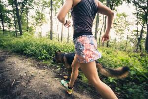 Trail running athletic woman in green forest, sports inspiration