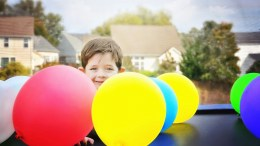 A young boy playing with balloons