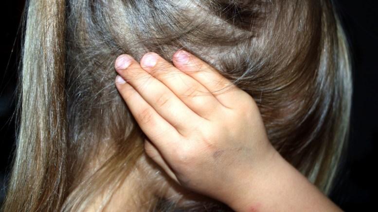 A girl covers her ears. Image by Ulrike Mai
