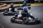 People drive karts around a track