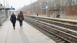 Two young people walk along a railway platform