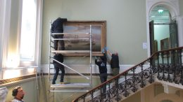 Maritime painting being removed from the walls in the main stairwell of the Maritime Museum