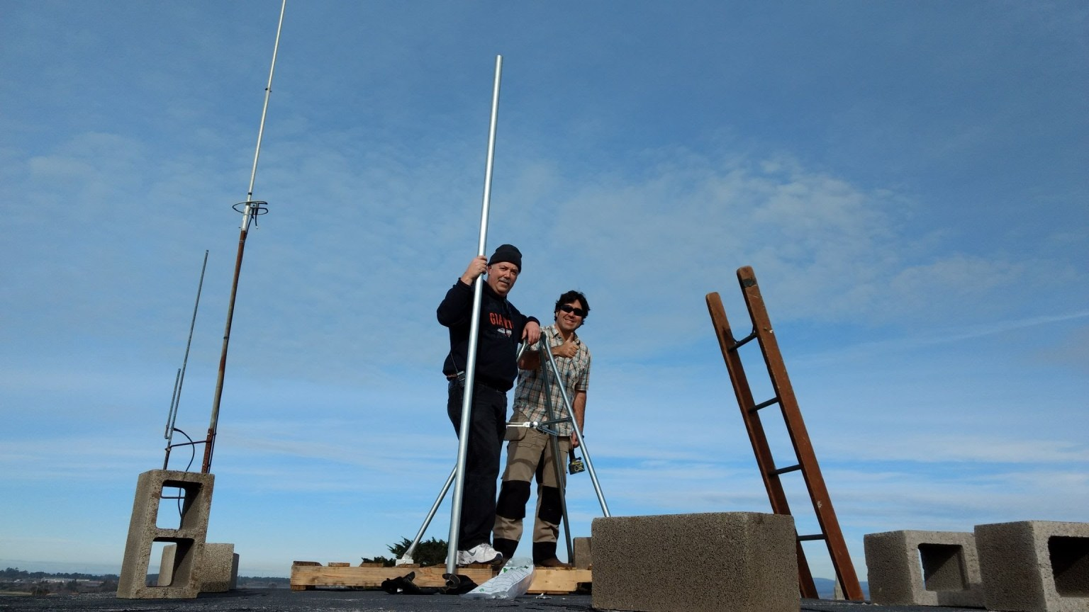 Two people erecting an antenna mast
