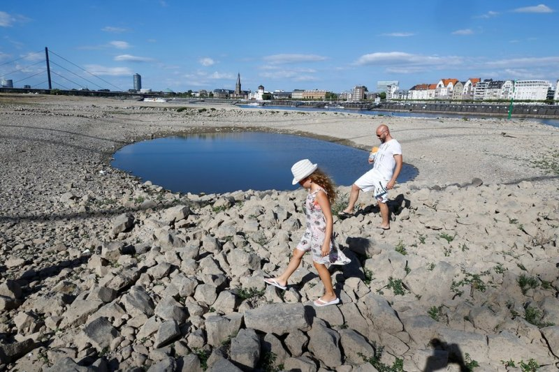 A family walks next to a puddle in the partially dried riverbed of Rhine, in front of the skyline of Dusseldorf, Germany