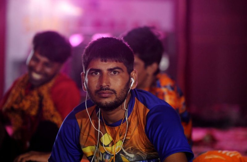 A Kanwariya rests while listening to music on his phone as others dance to religious songs at a camp in Delhi on 7 August 2018.