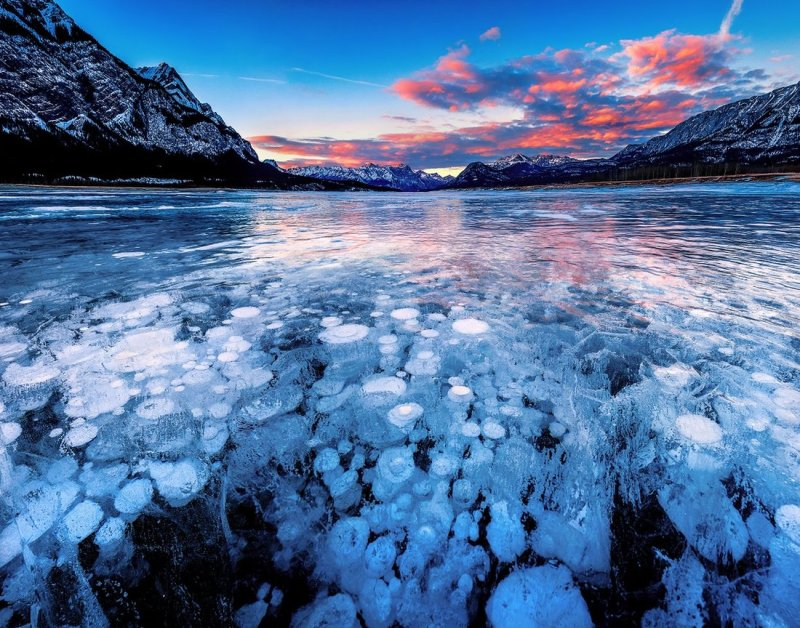 Burning sky and the panoramic view of the frozen Abraham Lake, Alberta, Canada at sunset. Stacks of bubbles trapped inside the lake look amazing.