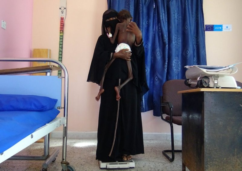 A woman holds her child whilst she stands on a scale
