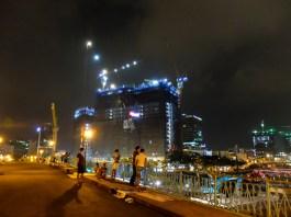 Мост над реката и осветен строеж, който вероятно ще е поредния небостъргач