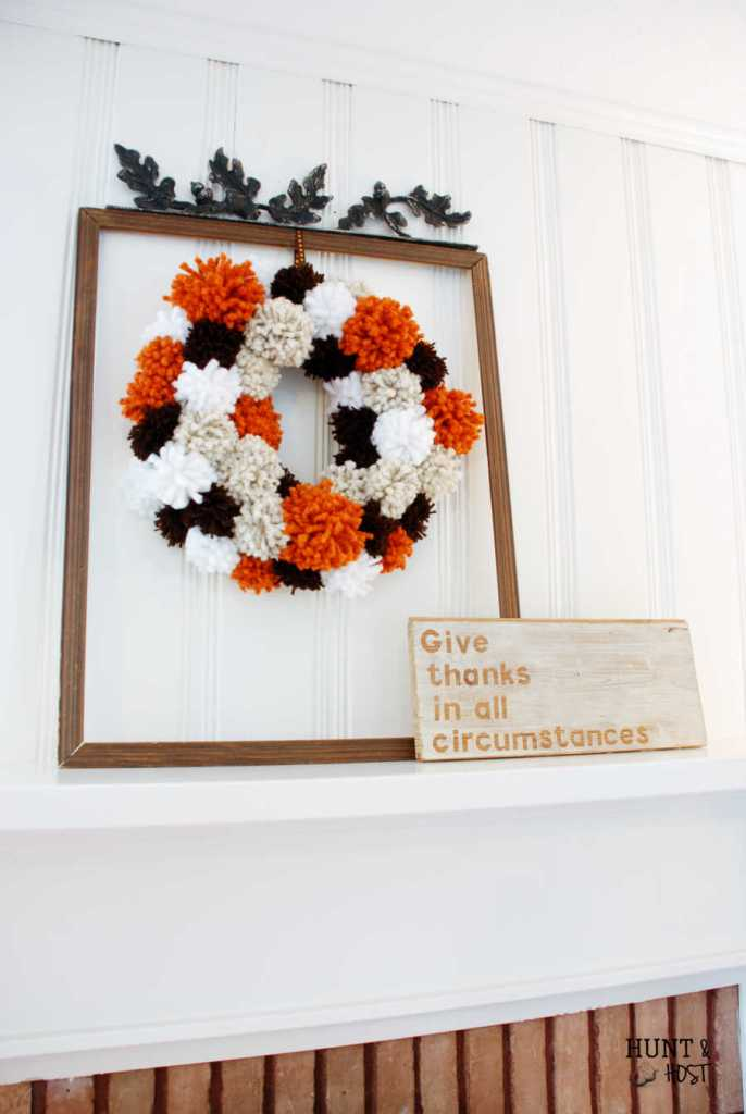 Cozy thoughts happen when you see this DIY Fall pom pom wreath. It's a knock out in stunning Autumn colors!