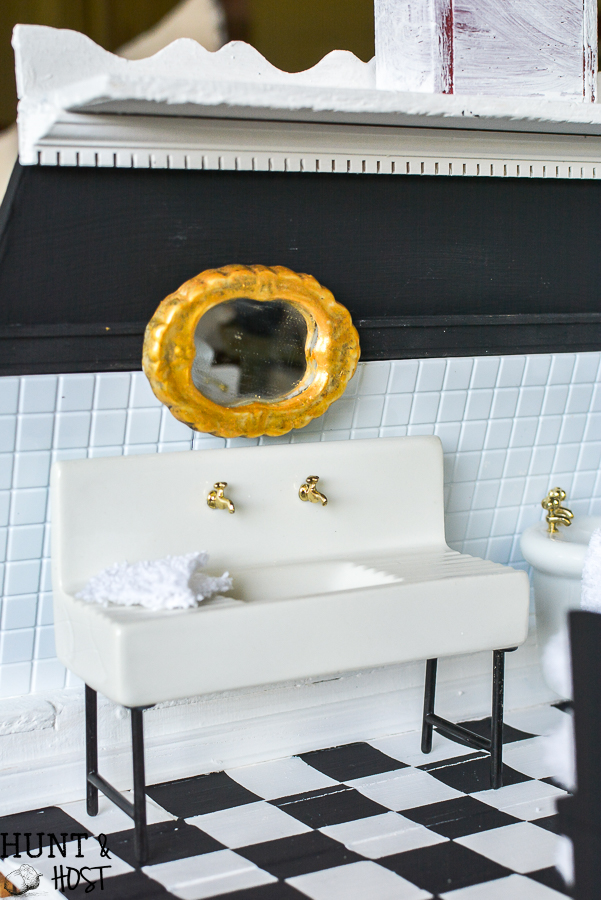 Dollhouse master bathroom decor ideas for a farmhouse bathroom. This tiny bathroom has it all, a claw tub, farmhouse sink, black and white checkered floor and cute DIY wall art.