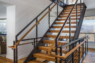 Hardwood stair treads with metal railing in modern home