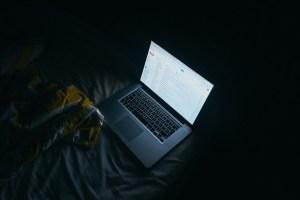 laptop open on bed in dark room