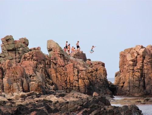 Klippor reser sig upp ur havet vid Hovs Hallar.