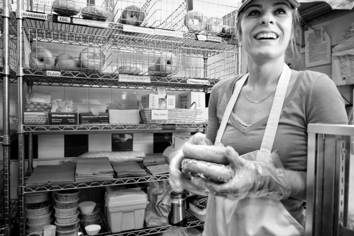 woman smiling holding bagels