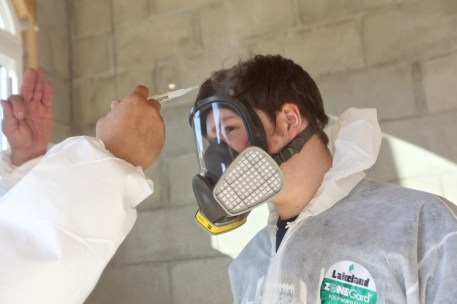 photo of man in a protective mask and bunny suit getting a respirator test