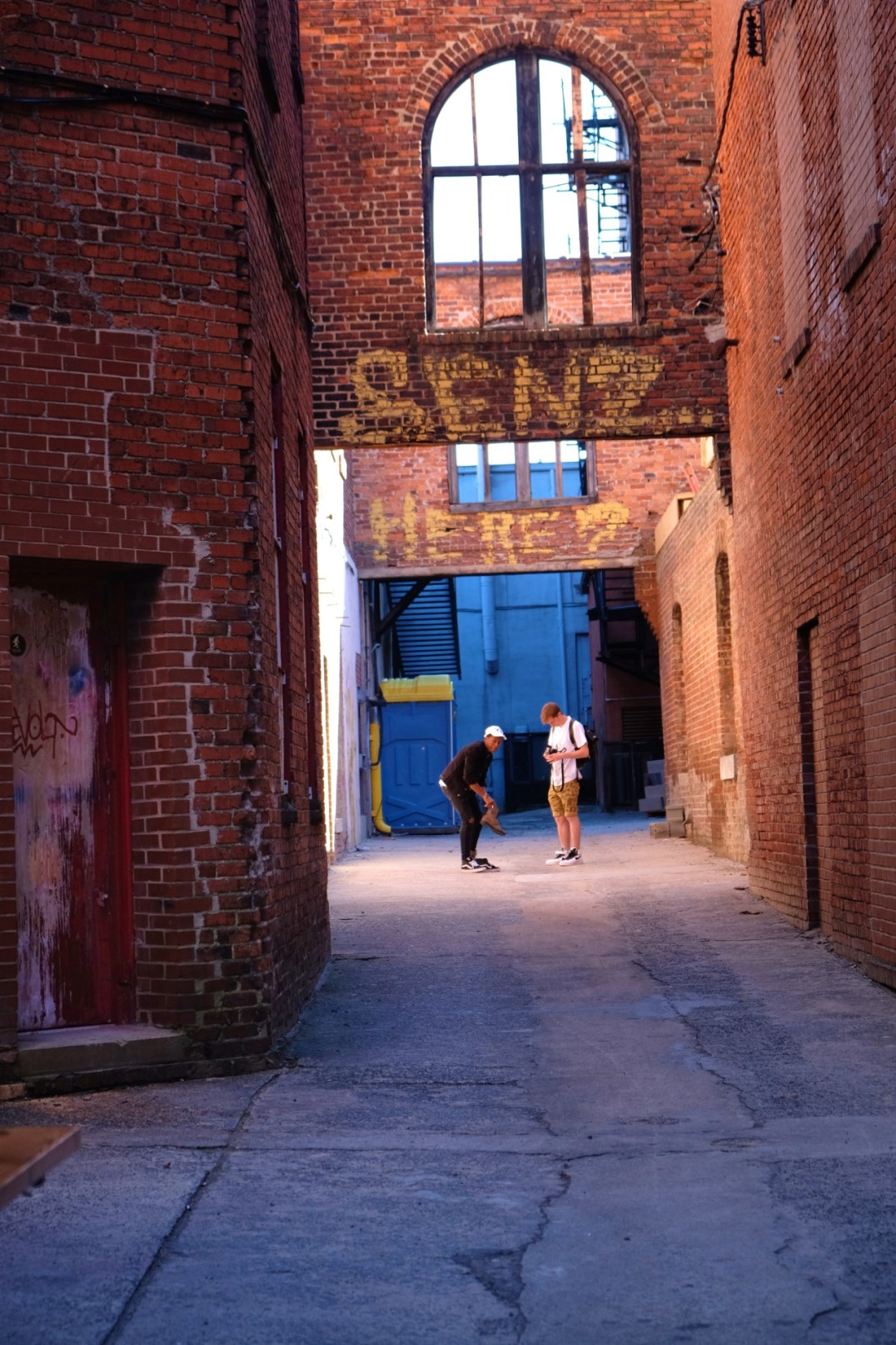 photo of two teen boys in a colorful alleyway