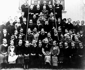 Hvasser 1881. Klassebilde Austheim skole. Lærer Gullik Pedersen og frøken Henden sitter i trappa midt på bildet. Elevene har vi ikke navn på. Kilde: Hvasser skole.