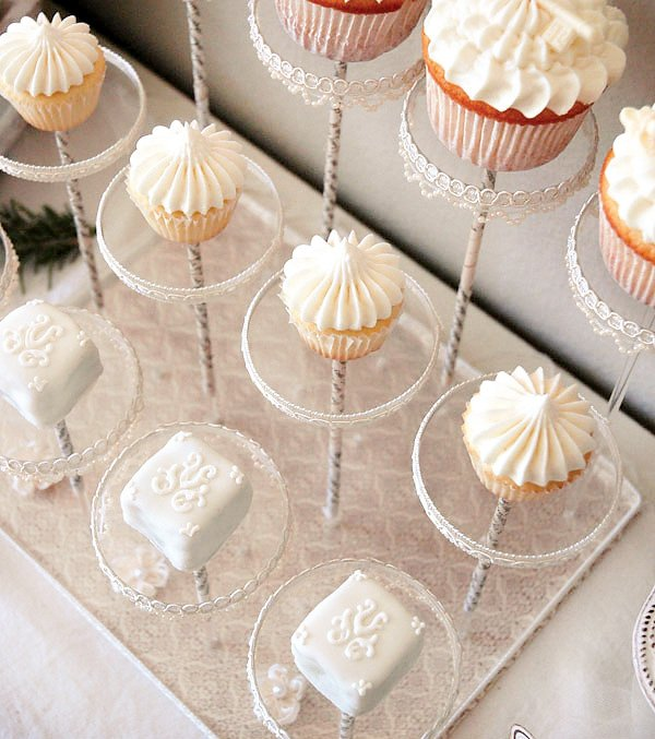 white winter cupcakes and petit fours on acrylic pastry pedestals