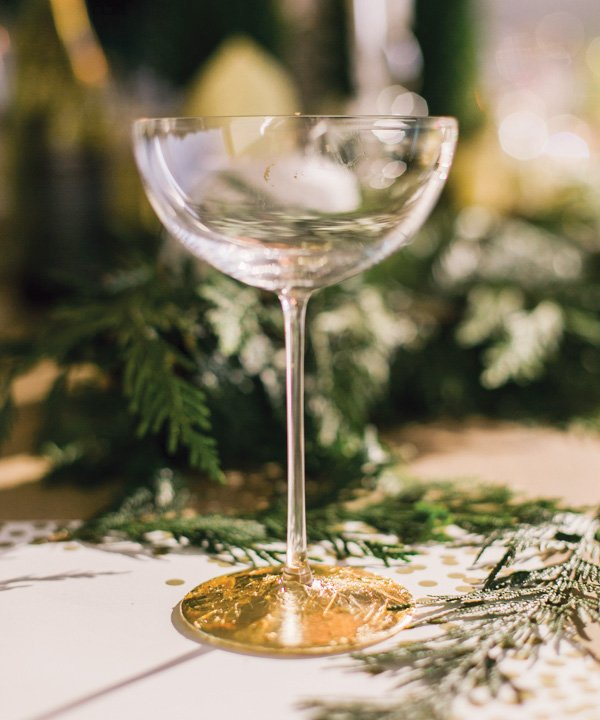 a champagne glass or cup with gold leaf added to the foot for a holiday or christmas craft