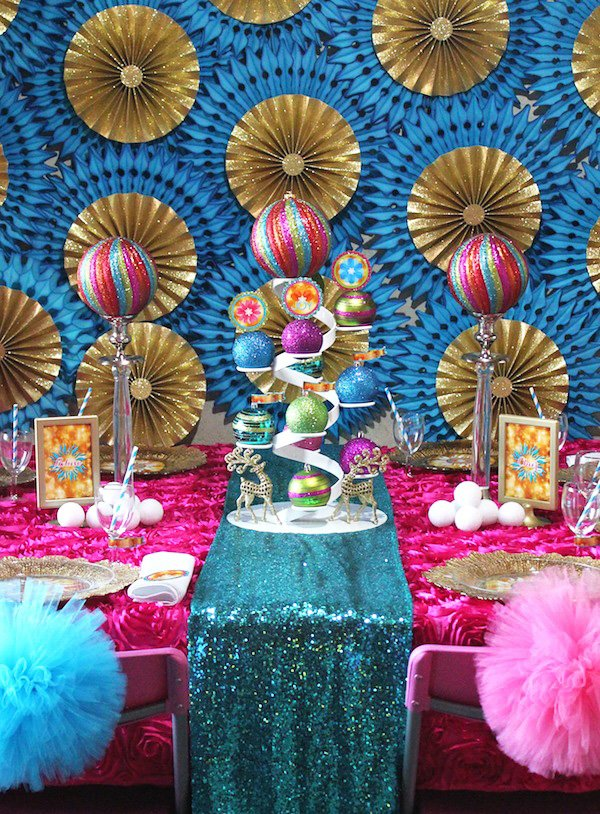 blue and gold paper fan backdrop behind a colorful tablescape with rainbow glittered ornaments
