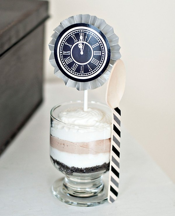layered dessert topped with clock and party circle