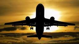 Airport solar power - sun behind airplane