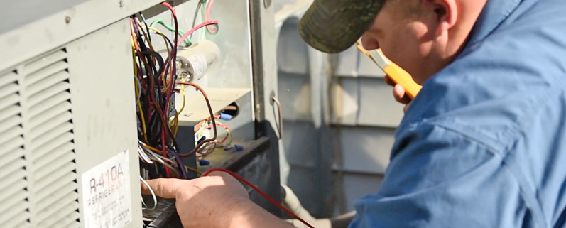 man repairing an air conditioning system