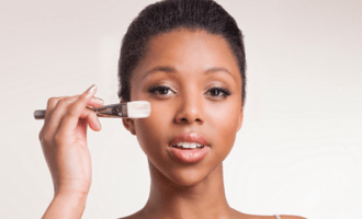 woman holding foundation brush near her cheek