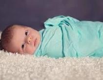baby with blue blanket