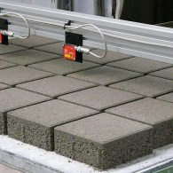 Quality control in the manufacture of concrete products using a block height measuring system to which a module can be added to determine the bulk density