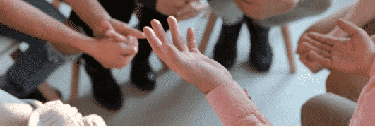 The hands and legs of people sitting in a circle during a support group