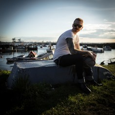 Young man sitting on upturned boat with harbour behind