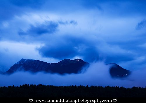 View of Krvavec mountain and ski resort (1854m) and Kalski Greben mountain (2224m) part of the Kamnik Alps breaking through the clouds at dusk after a day of heavy rain, Slovenia. Seen from Brnik, near the Ljubljana airport.