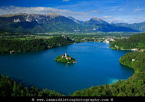 View across Lake Bled to the island church and clifftop castle from Mala Osojnica, Slovenia.