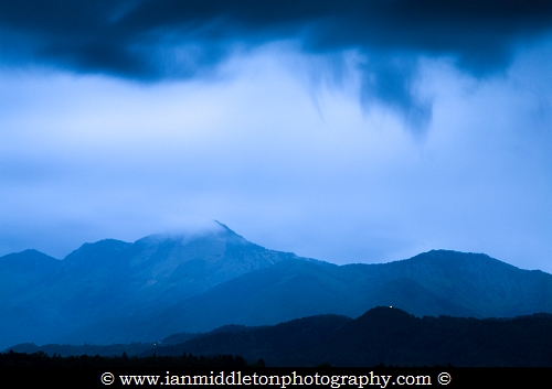 View of Storzic mountain, part of the Kamnik Alps, as storm clouds gather overhead at dusk, Slovenia. Seen from Brnik, near the Ljubljana airport. The tiny glow of a hilltop church, lit up at dusk, is also visible in the lower right corner. In Slovenia, as with most mountainous places, you can't look at a mountain view without it being dotted with churches.