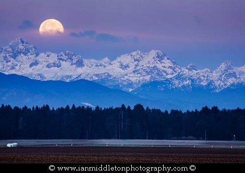 Full Moon setting over the Julian Alps in the morning, Brnik, Slovenia.