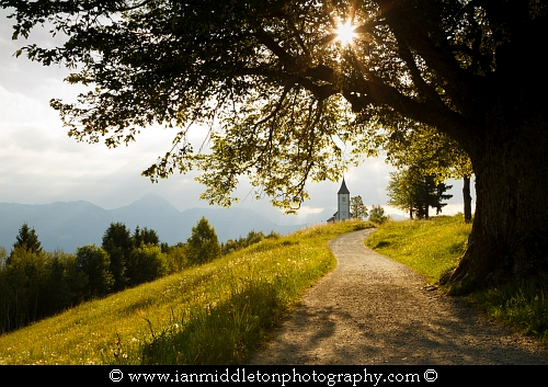 Jamnik church of Saints Primus and Felician, perched on a hill on the Jelovica Plateau with the kamnik alps and Karawanke mountains in the background, Slovenia.