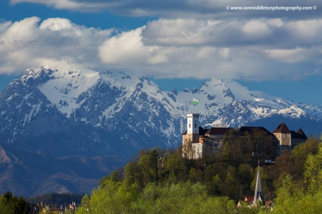 View across the city to Ljubljana Castle with the snowcapped Kamnik Alps forming a picture perfect background. Ljubljanski Grad sits on a hill in the centre of the city overlooking the capitals old town.
