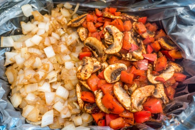 Cooked onions, mushrooms, and peppers in the slow cooker for homemade goulash