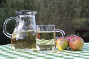 a mug, glass and apples