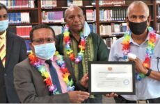 Minister for Higher Education, Research, Science and Technology Hon Wesley Raminai presenting to Sir Mick Nades, Founder of IBS Group the Certificate of Registration. Looking on is the Vice Chancellor Dr Ramachandran Arunachalam and Chancellor Ambassador Gabriel Pepson.