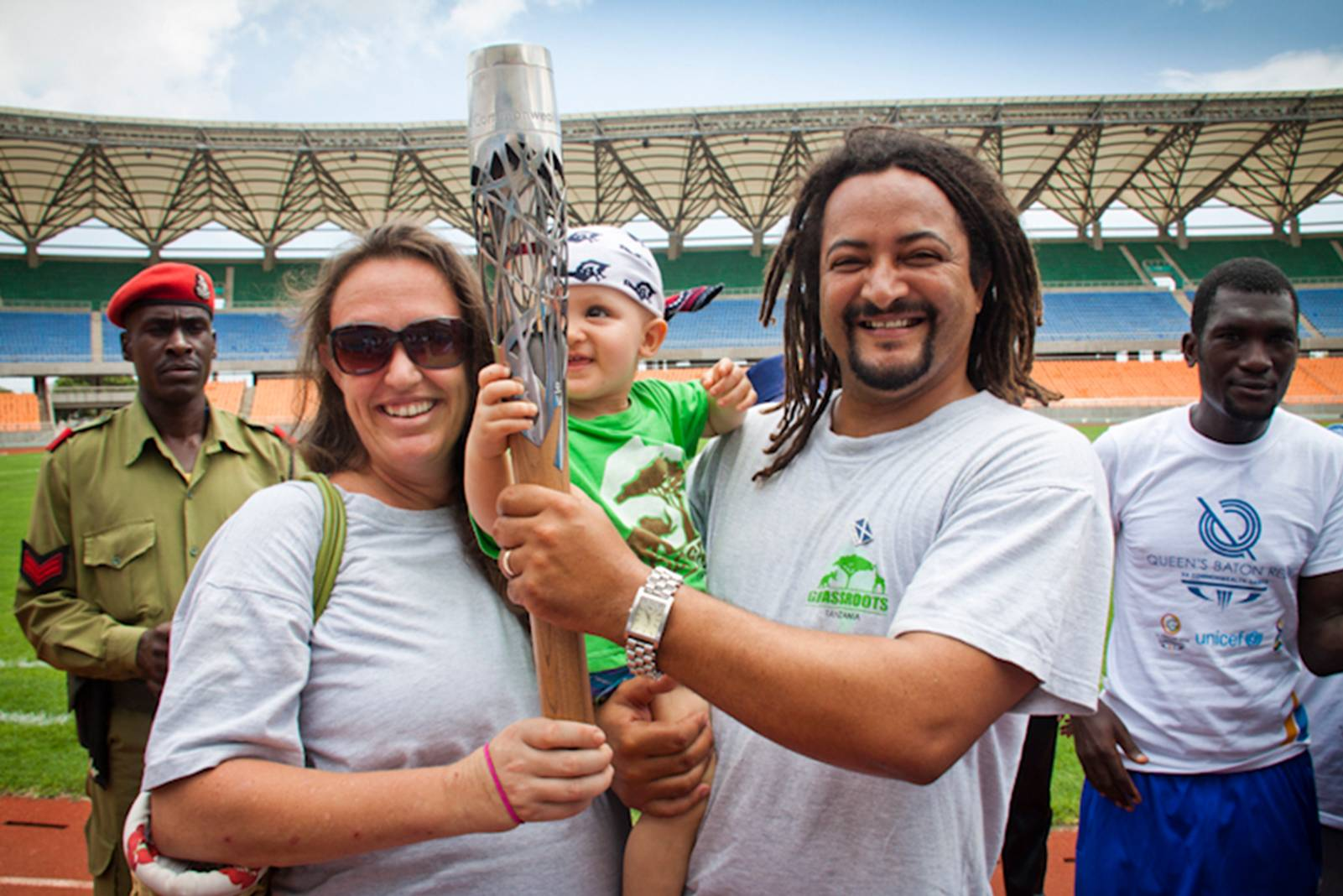 woam, child and man holding commonwealth torch inside atheletic stadium